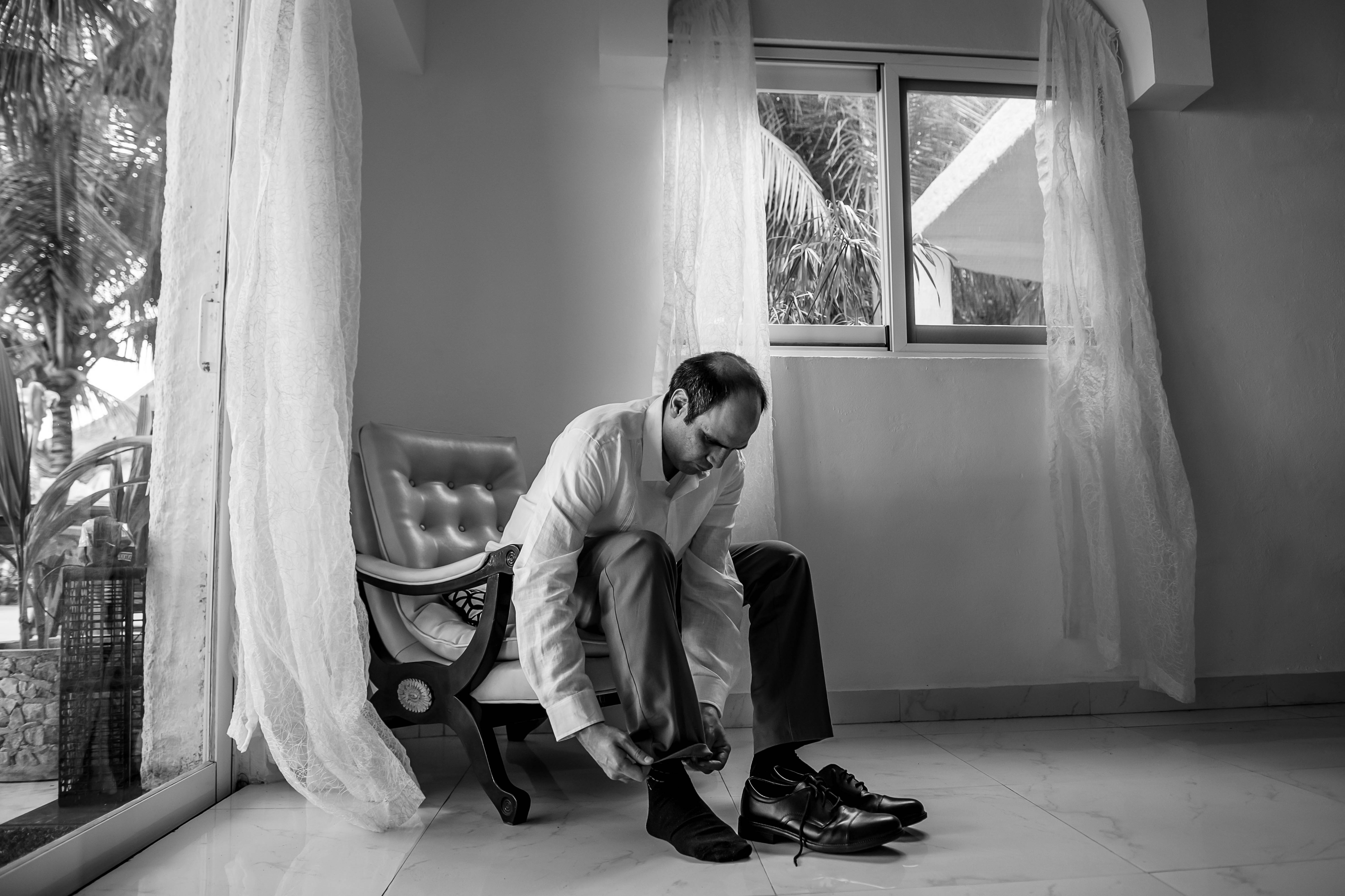 the groom putting the shoes before a ceremony at Ocean Events Cancun