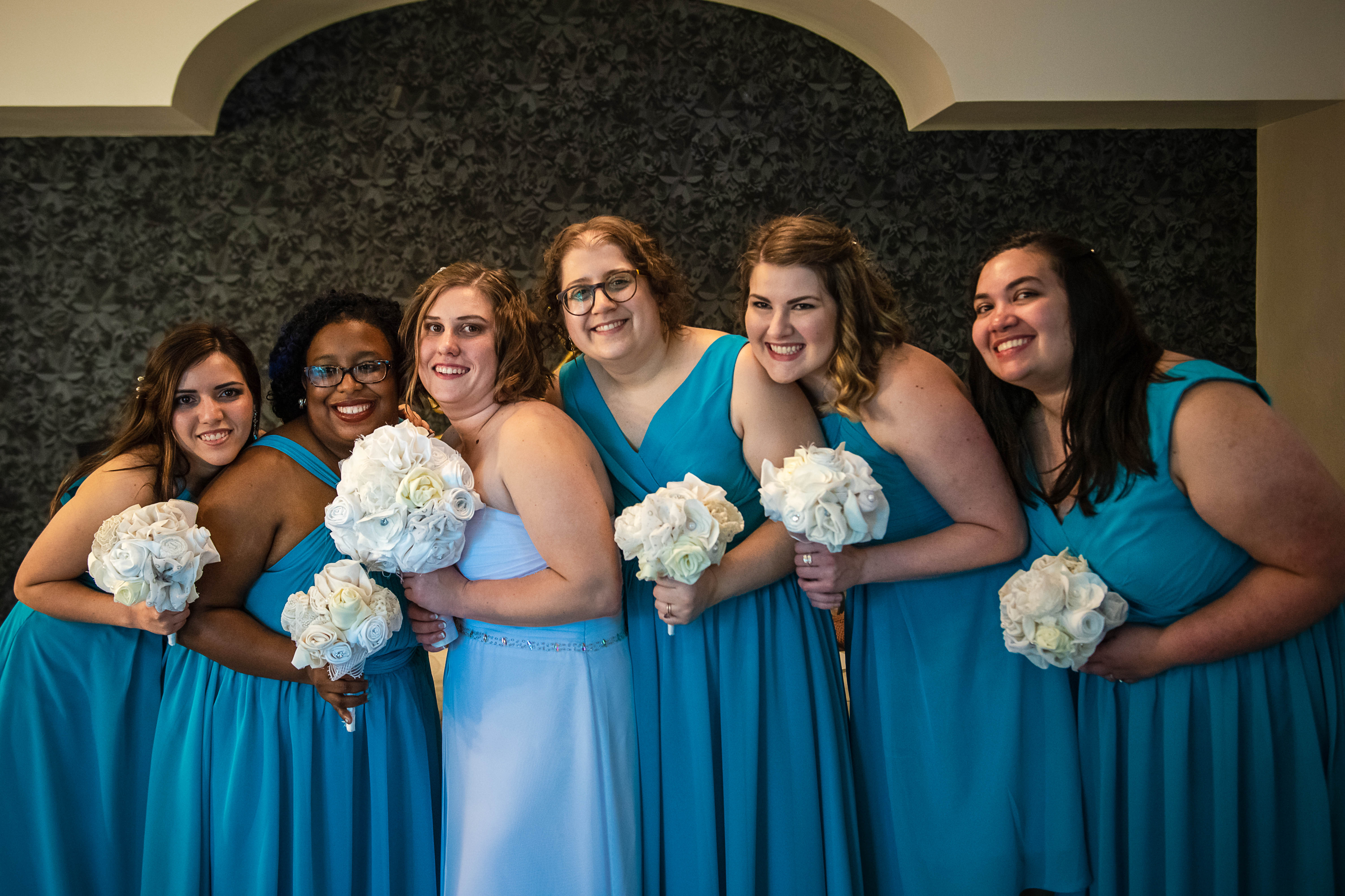 the bride with the bridesmaids and their flowers posing and smiling for the photo in Ocean Events Cancun