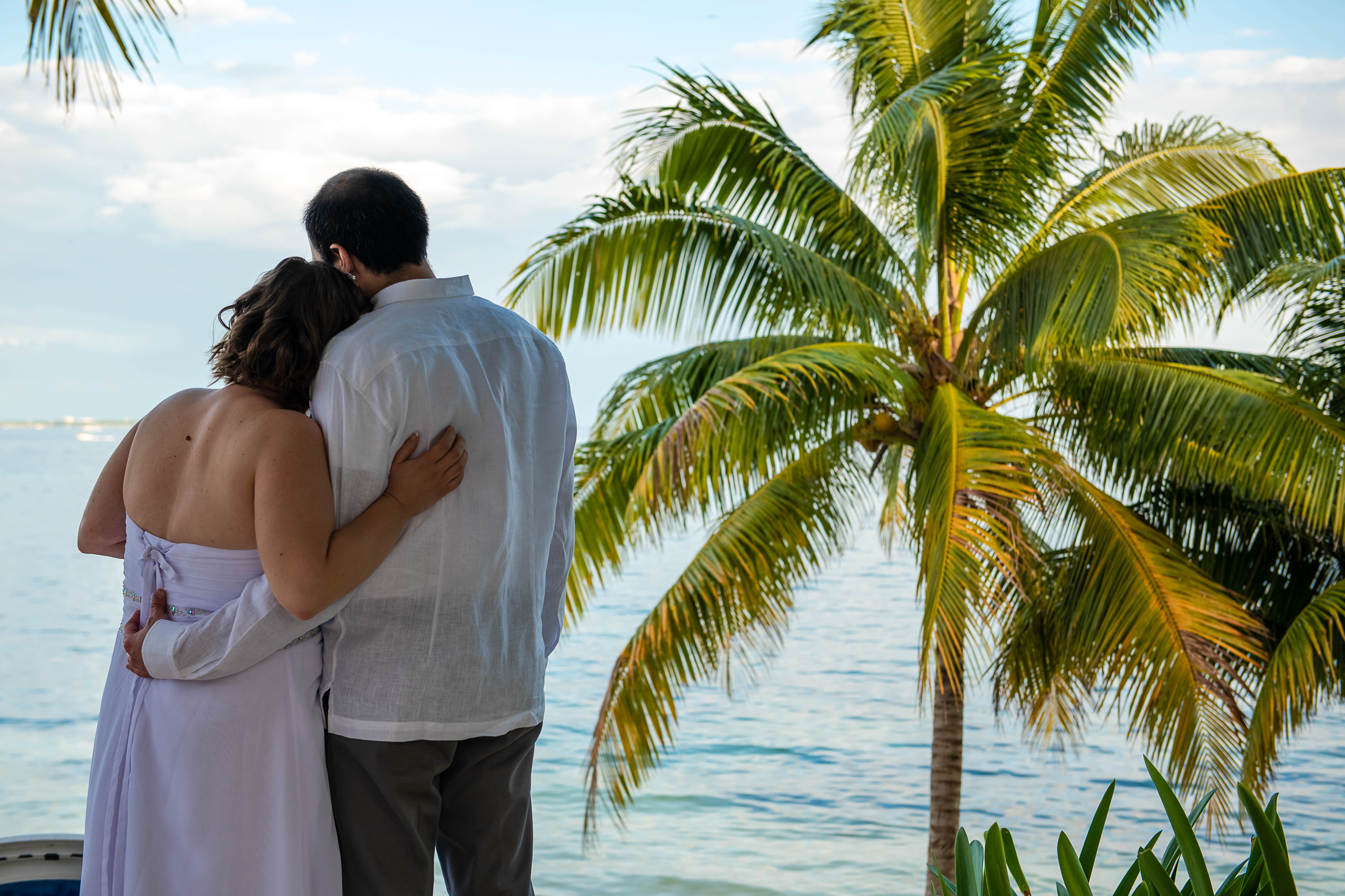 bride & groom during the first look  photo session looking at the ocean with a palms in Ocean Events Cancun