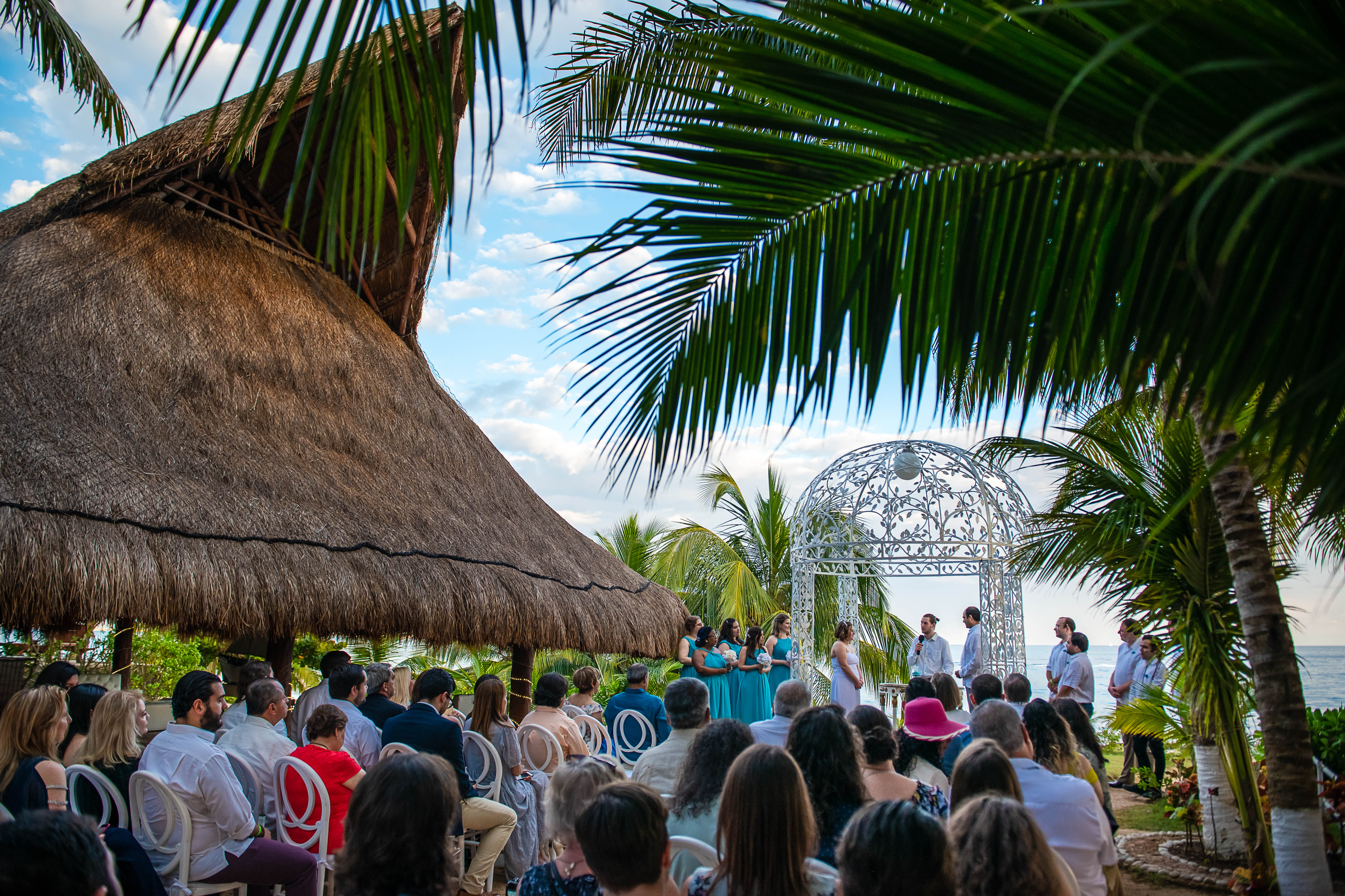 The ceremony in Ocean Events Cancun at the sunset with bride at groom looking to each other with the palms the gazebo and palapa