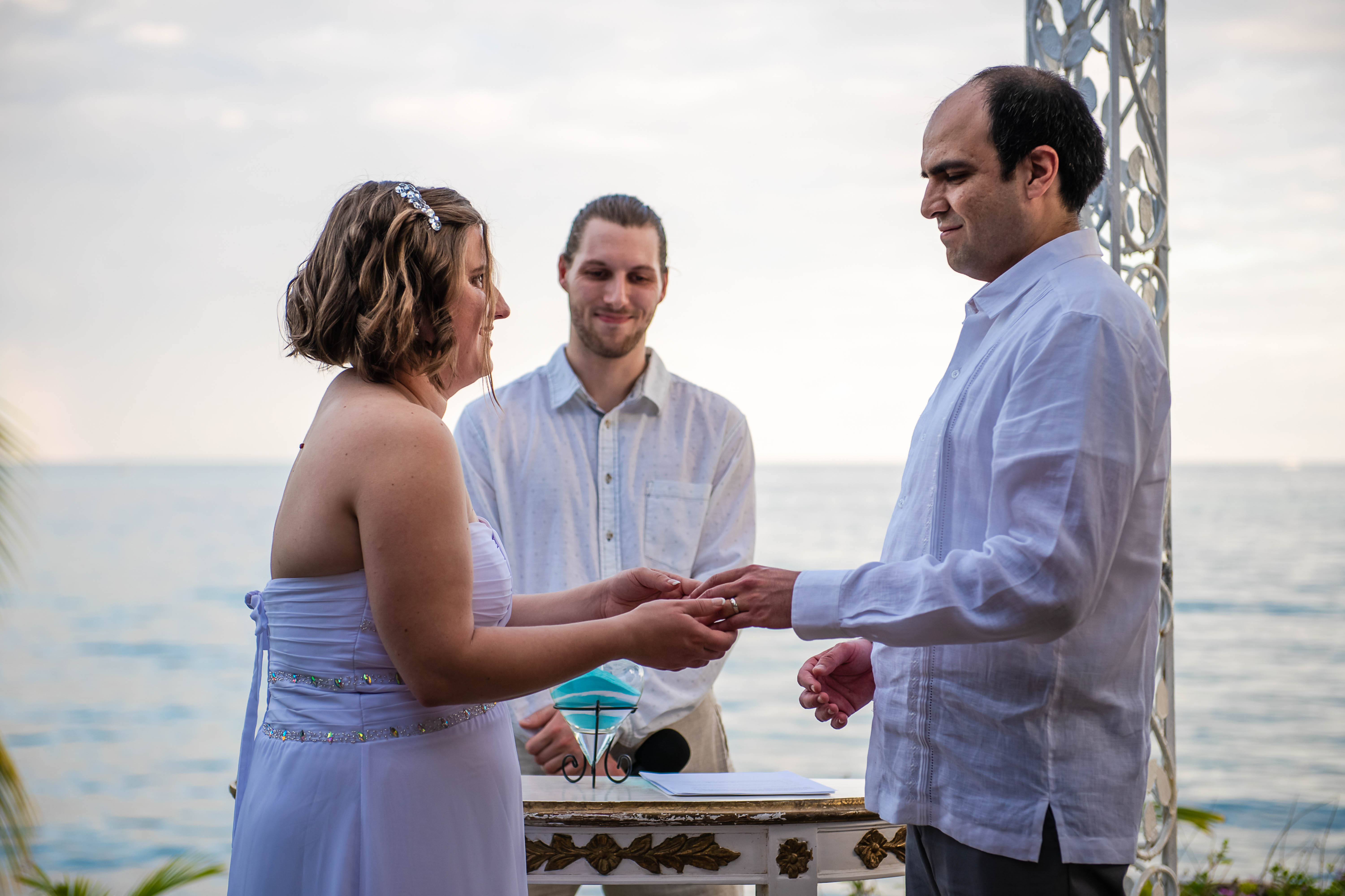 bride & groom giving to each other the rings and with the view to the see at Ocean Events Cancun