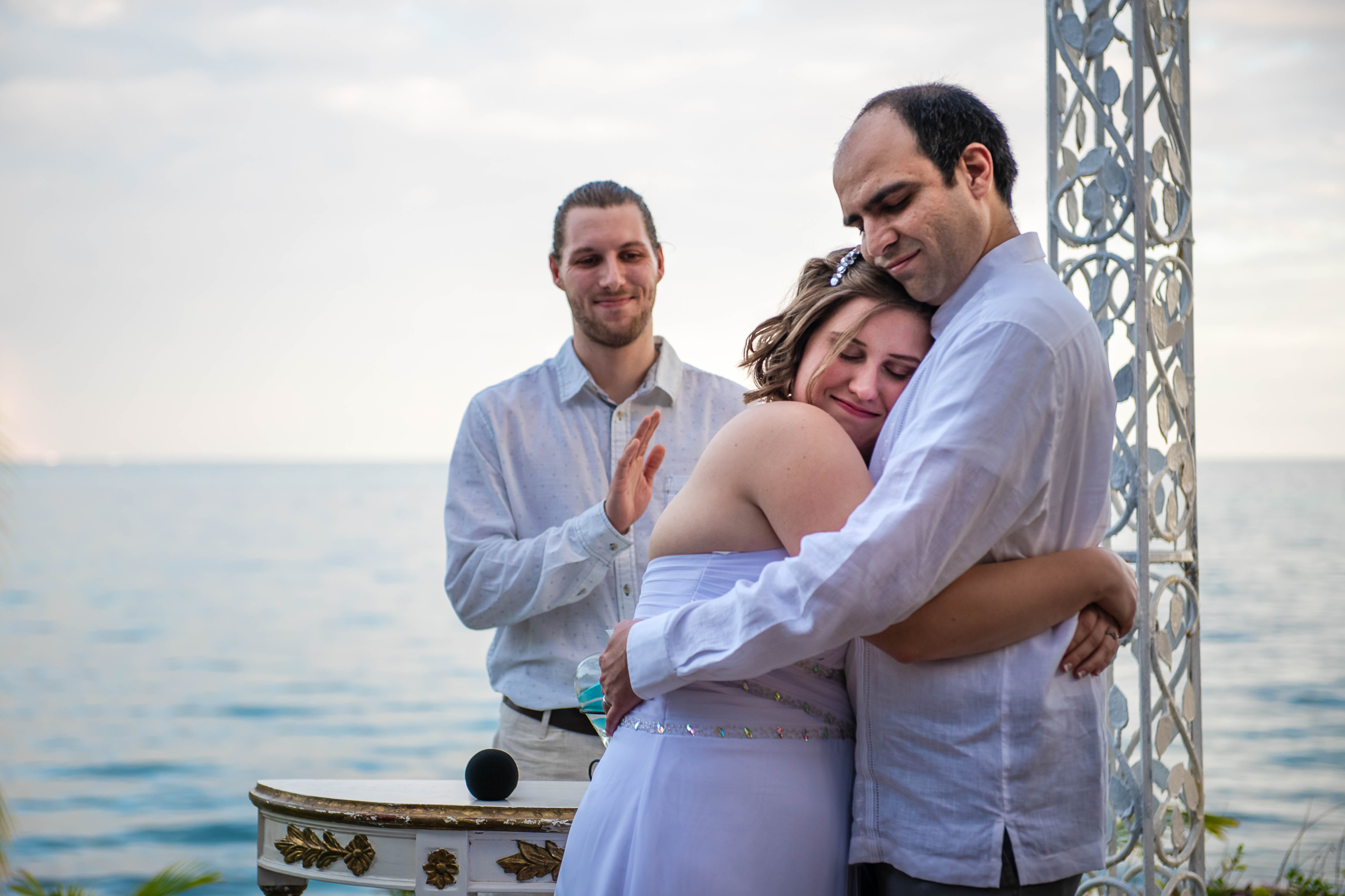 bride & groom giving a love hug and with the view to the see at Ocean Events Cancun
