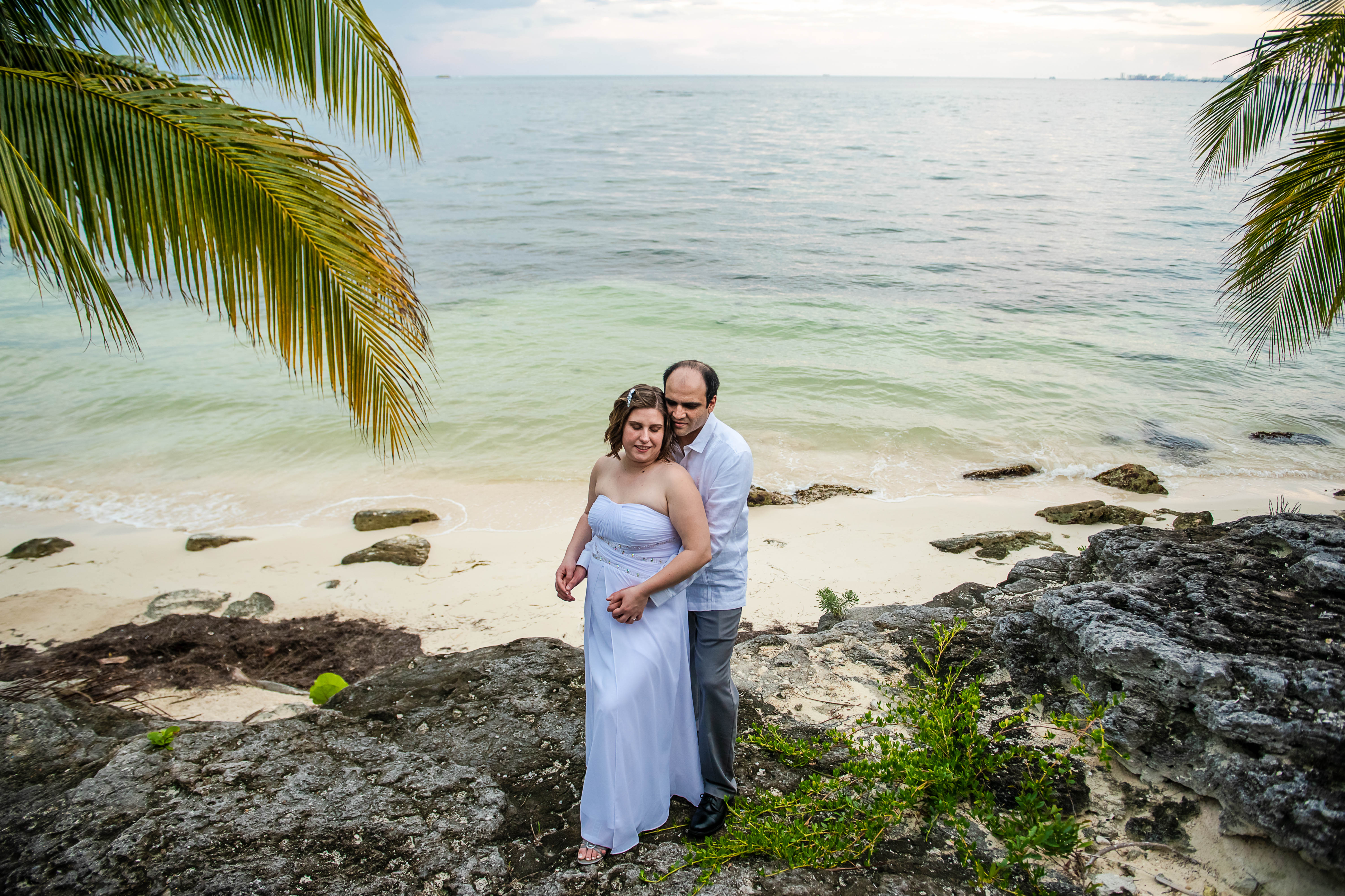 bride and groom posing to their portraits with the blue ocean and green palms and rocks in Ocean Events Cancun