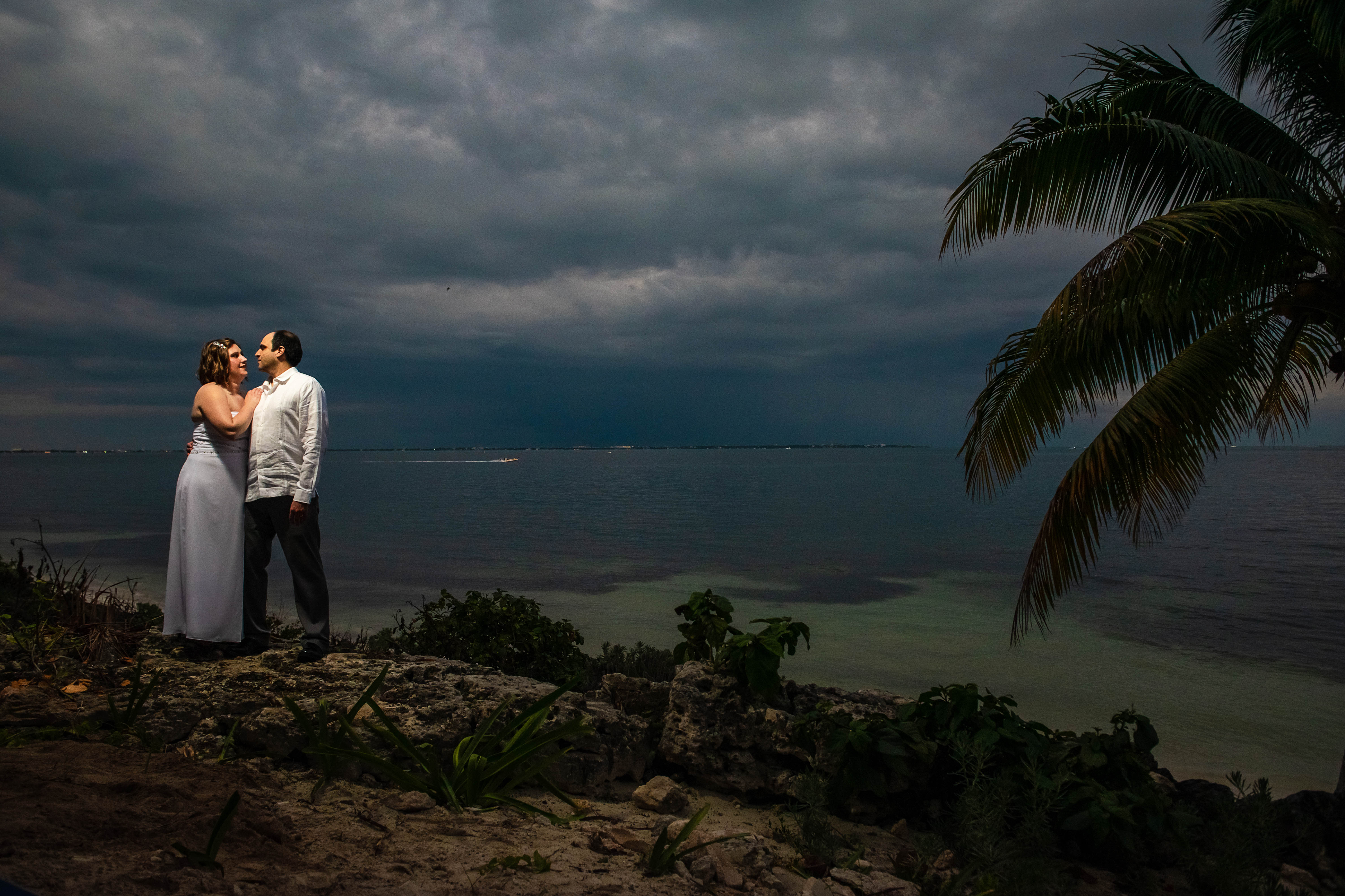 bride and groom posing to their portraits at the sunset with the blue ocean and green palms and rocks in Ocean Events Cancun