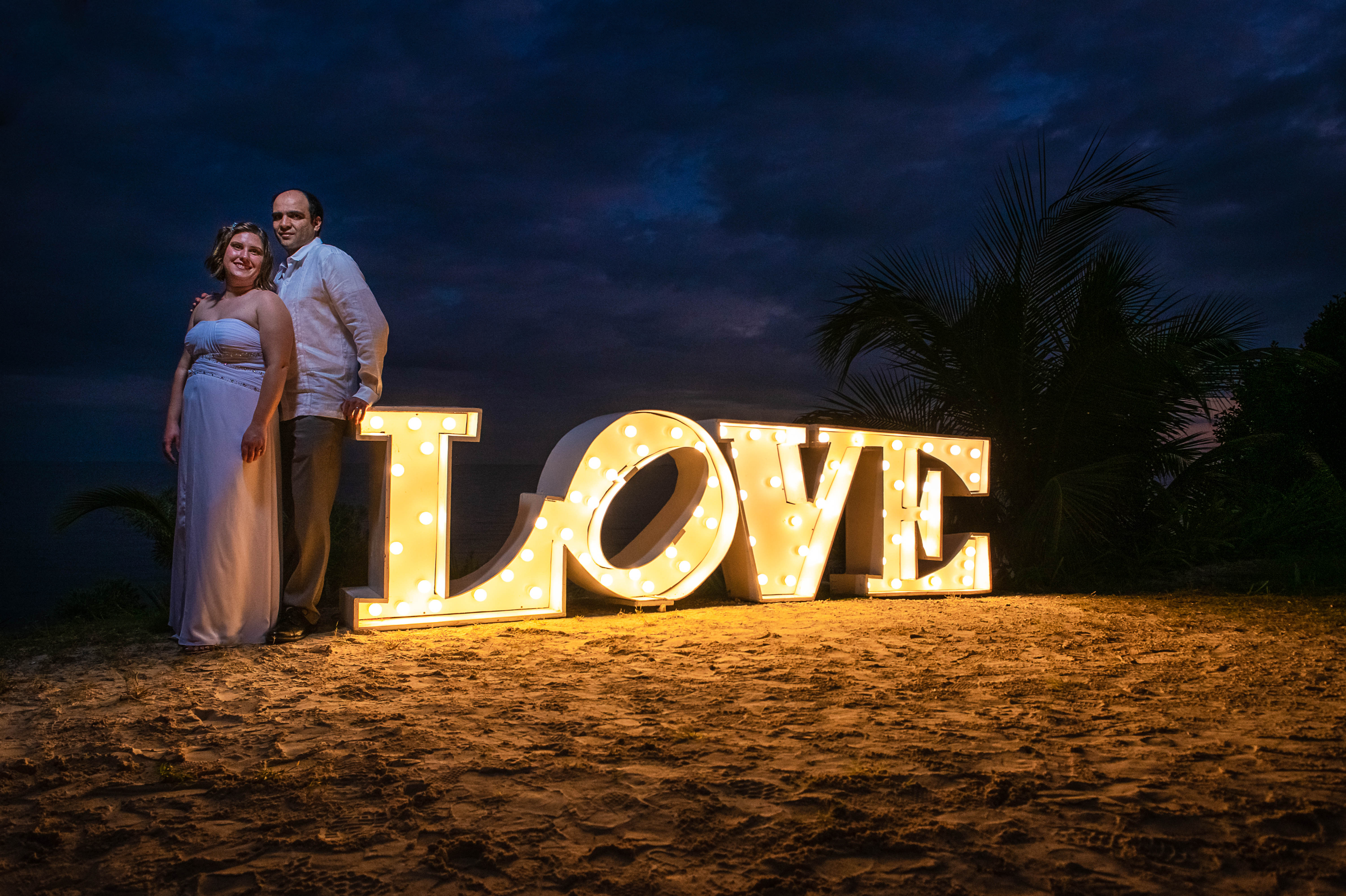 bride and groom posing to their portraits with the love sign and the blue ocean and green palms and rocks in Ocean Events Cancun