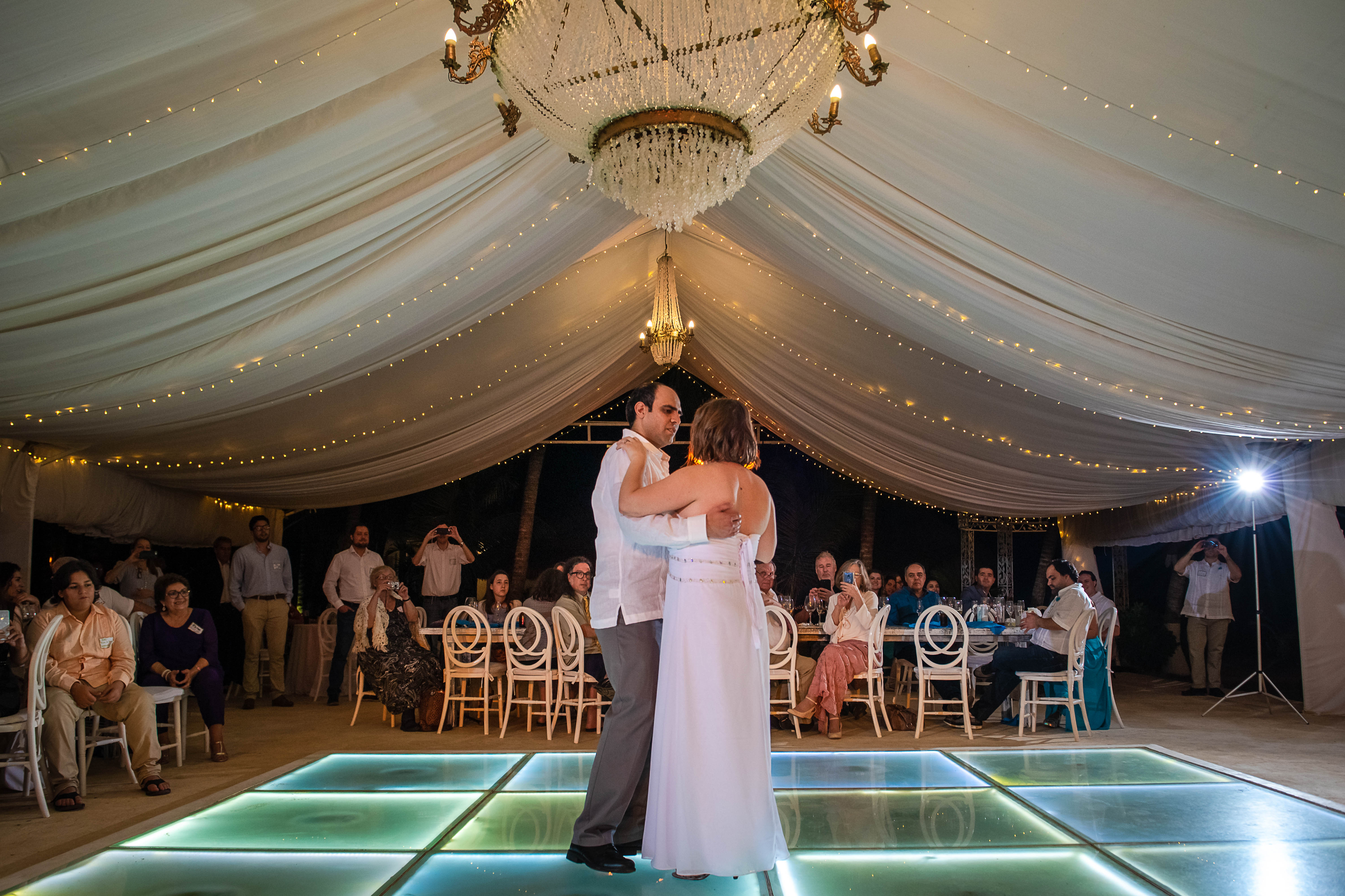 the bride and groom at the first dance as a husband and wife dancing at the dance flore with all the people looking them at Ocean Events Cancun