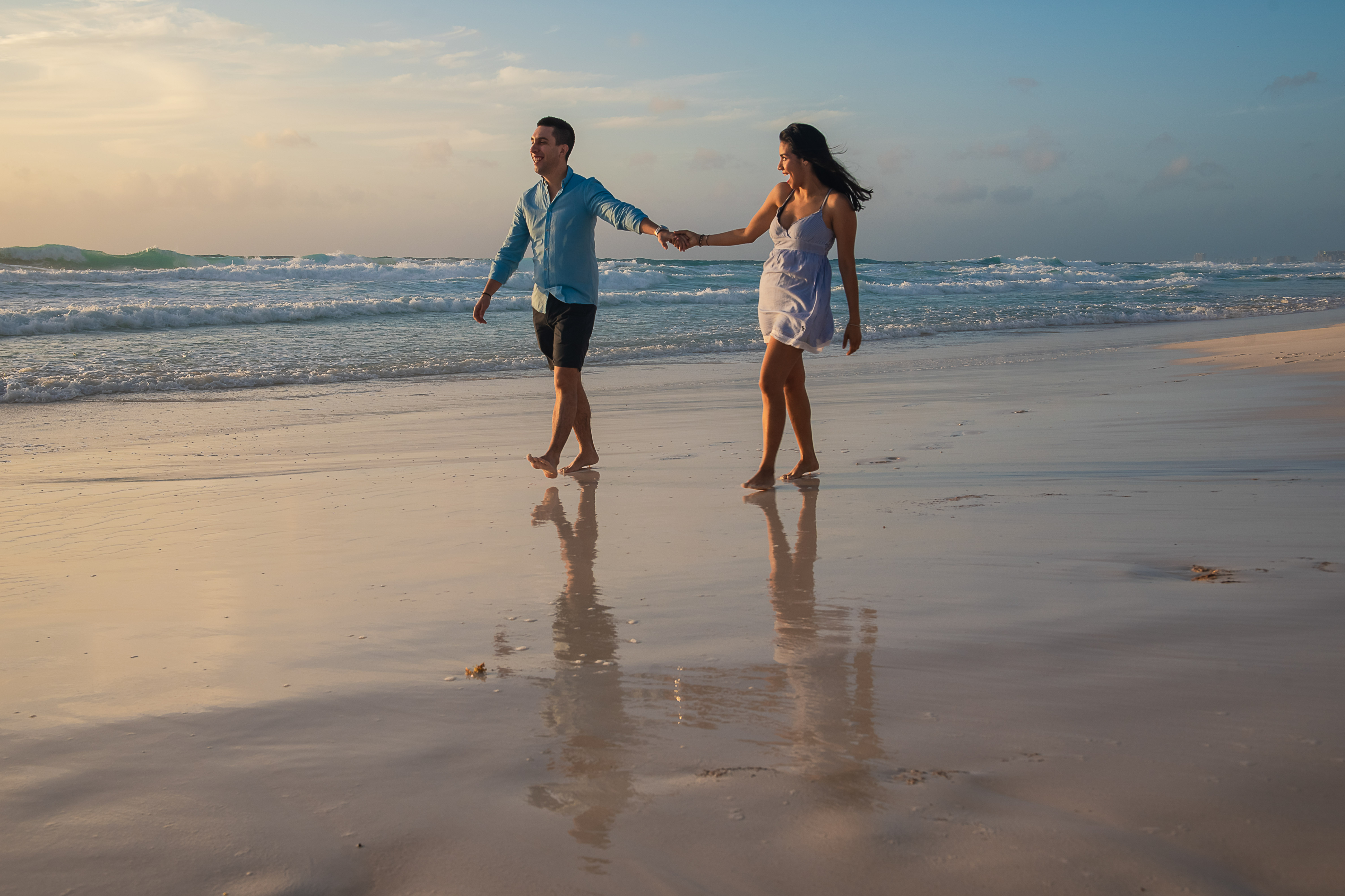 a couple holding their hands having fun at the beach with reflect in the sand in cancun