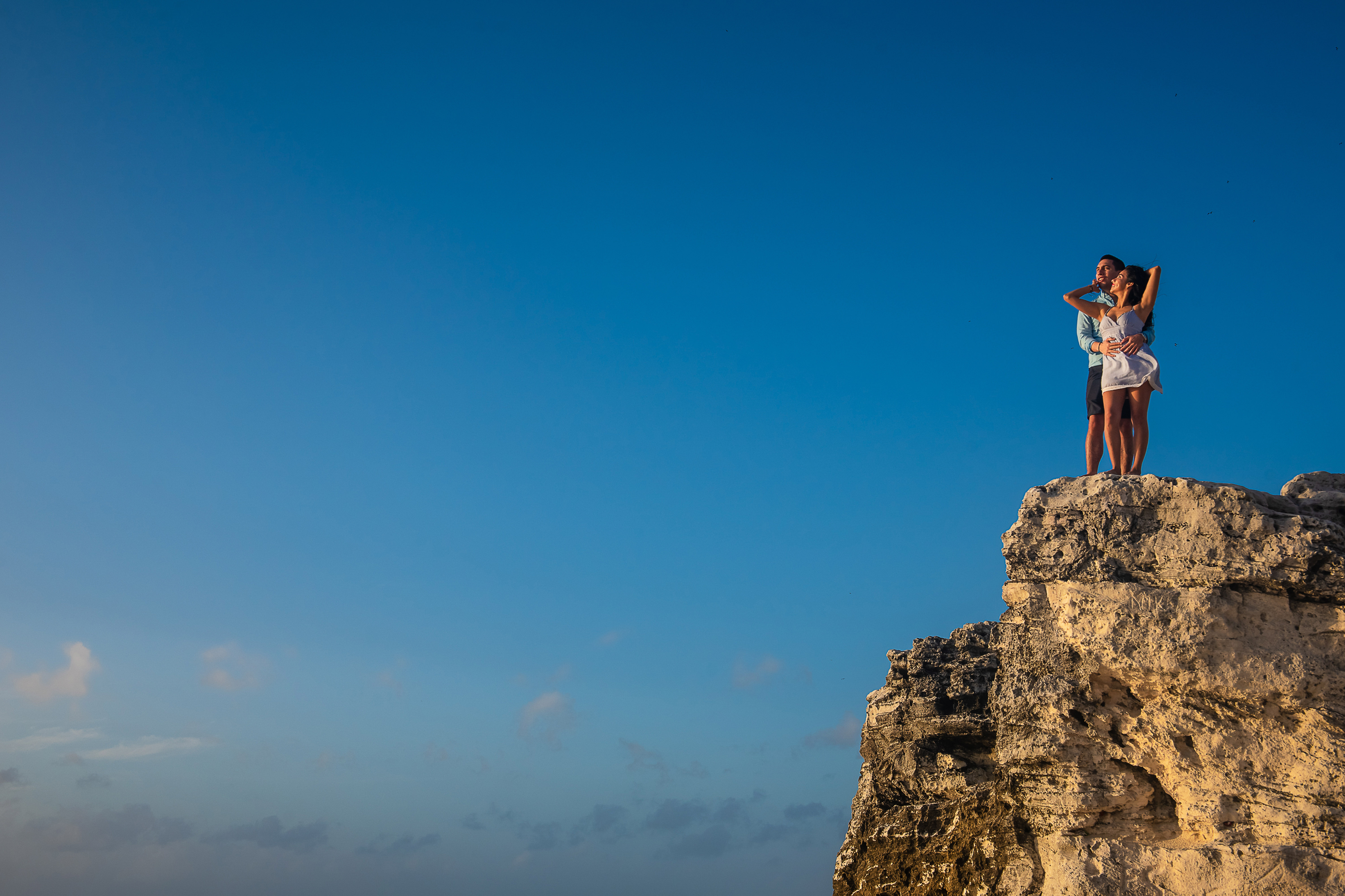 a couple posing in a big rock with blue sky in cancun