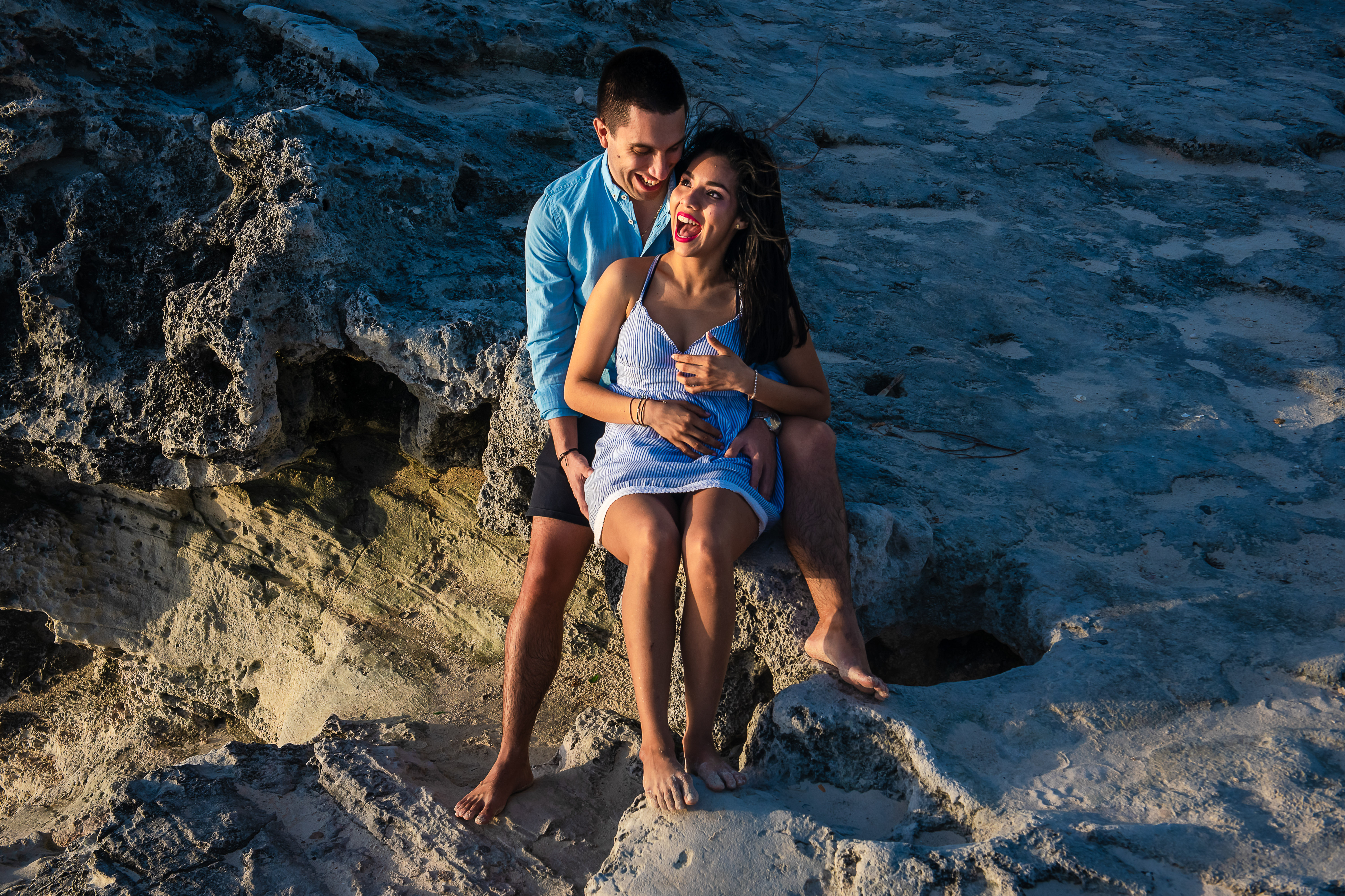 couple smiling sitting on the rocks dressing in blue and smiling in cancun