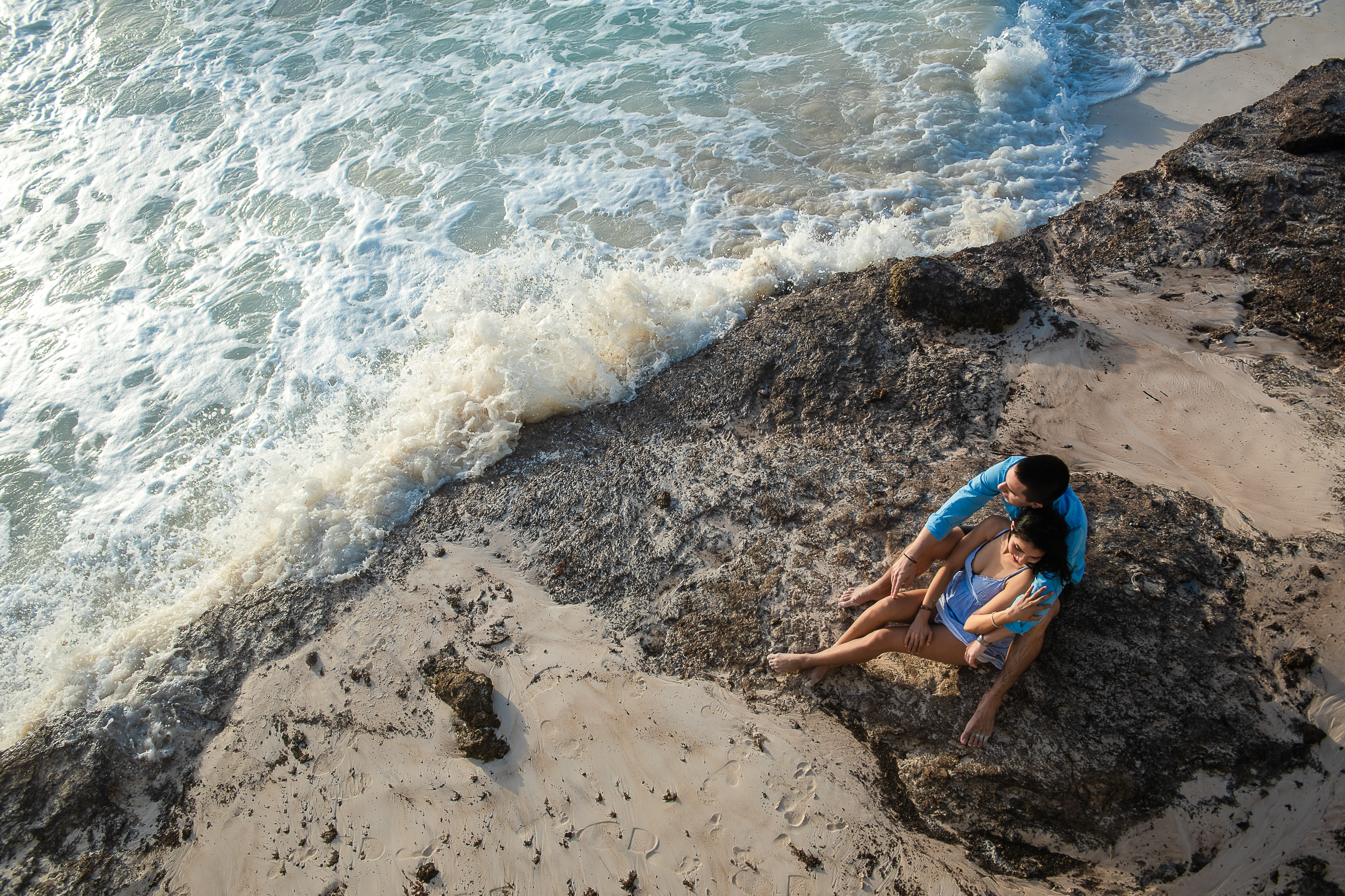 couple smiling sitting on the rocks dressing in blue and smiling looking at the see in cancun