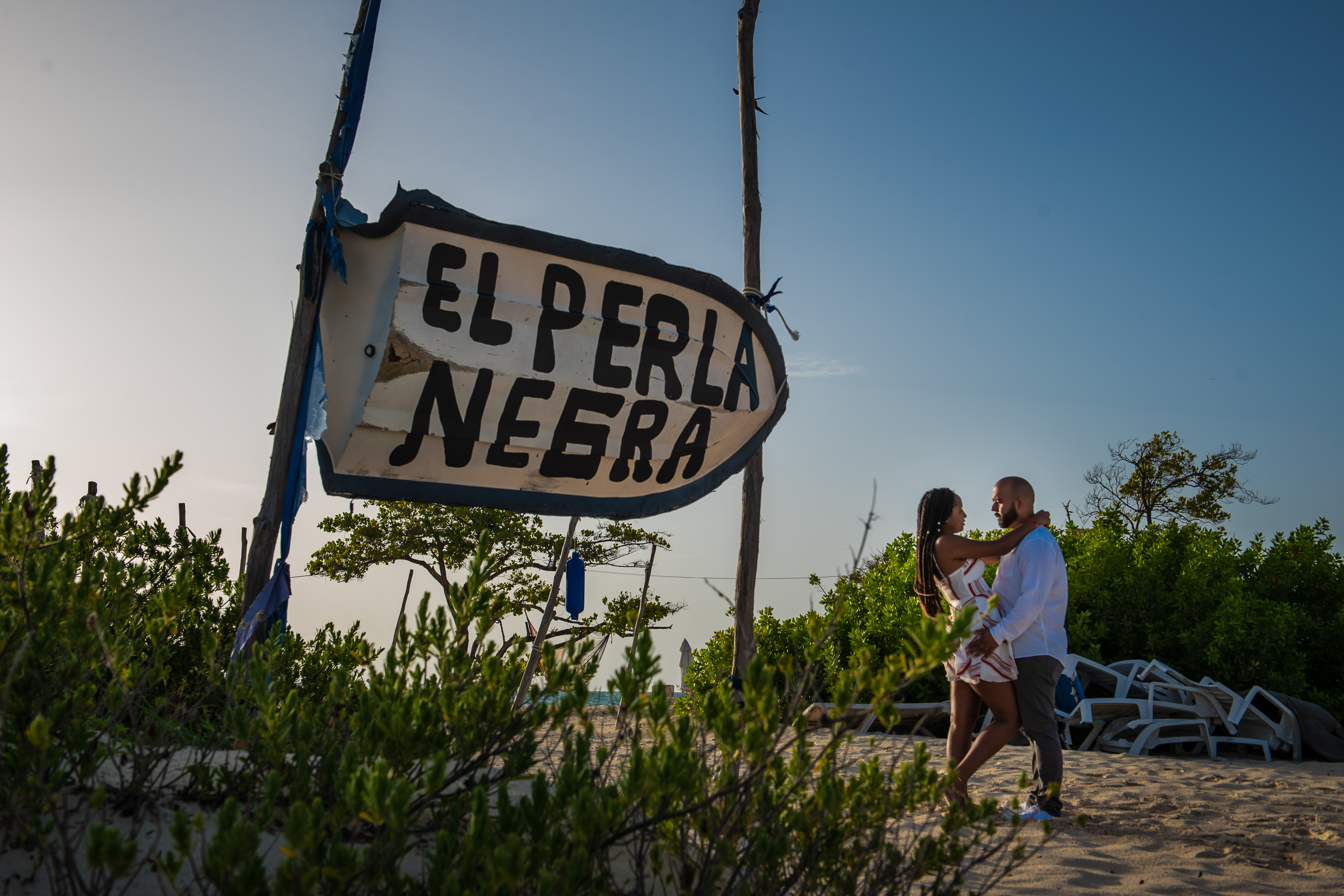 couple posing in paradise beach between trees and a bote at Isla Blanca and Costa Mujeres Quintana Roo