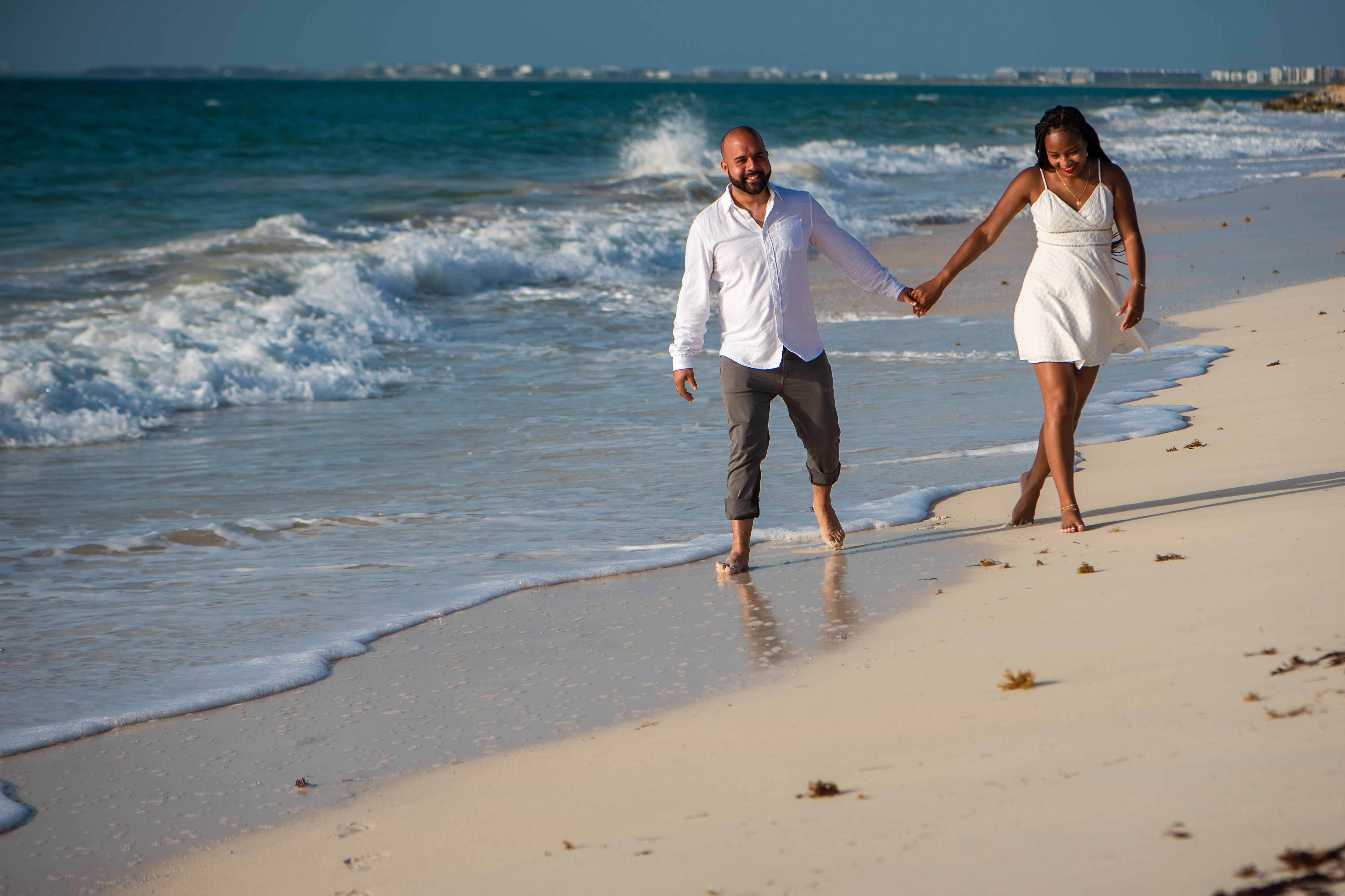 couple holding hands and walking at the beach in Isla Blanca Cancun smiling and having fun at Riu Costa Mujeres Hotel
