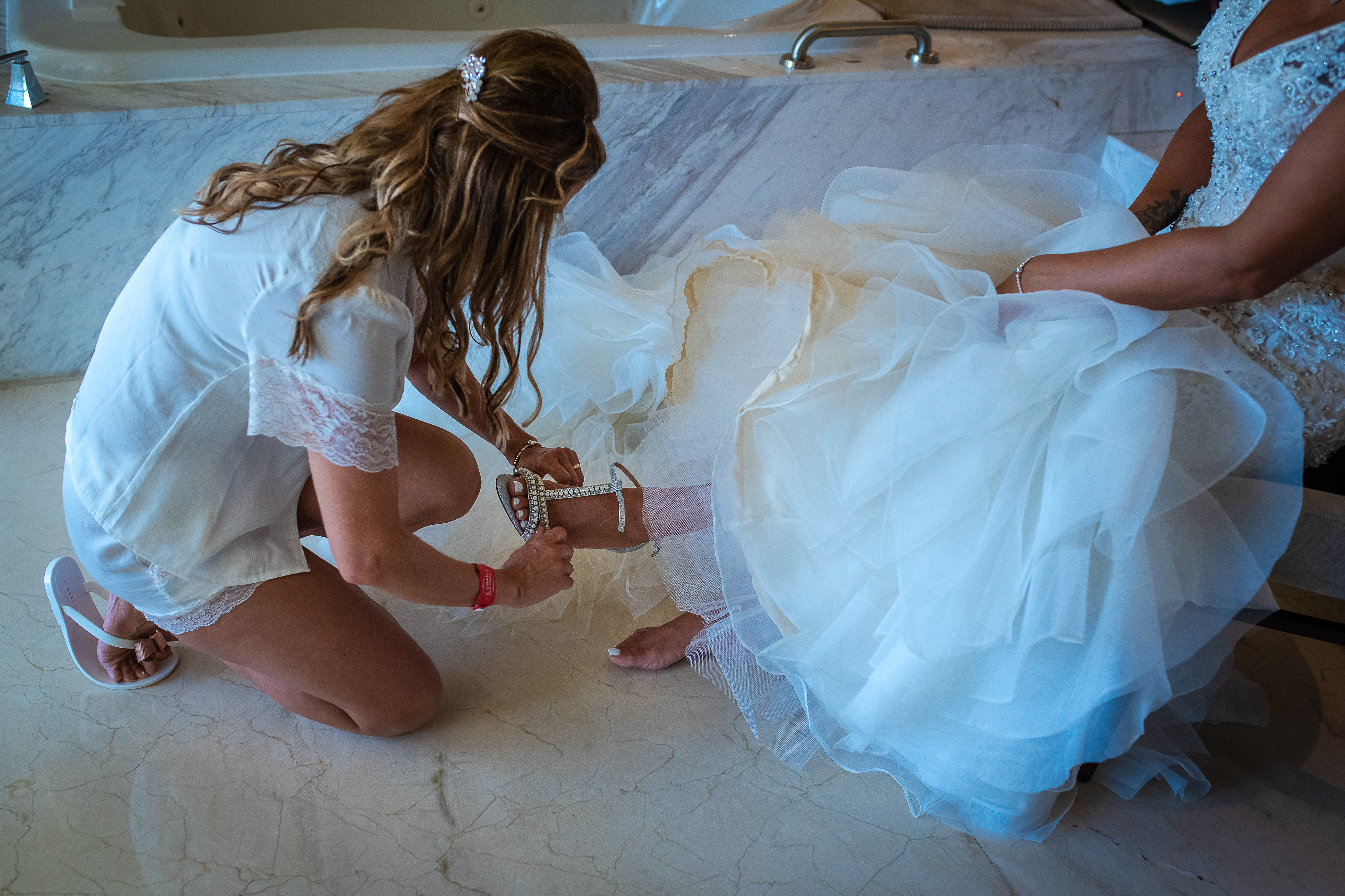 the main of honor during the getting ready helping to the bride to putting on the bride shoes in the gran at moon palace resort