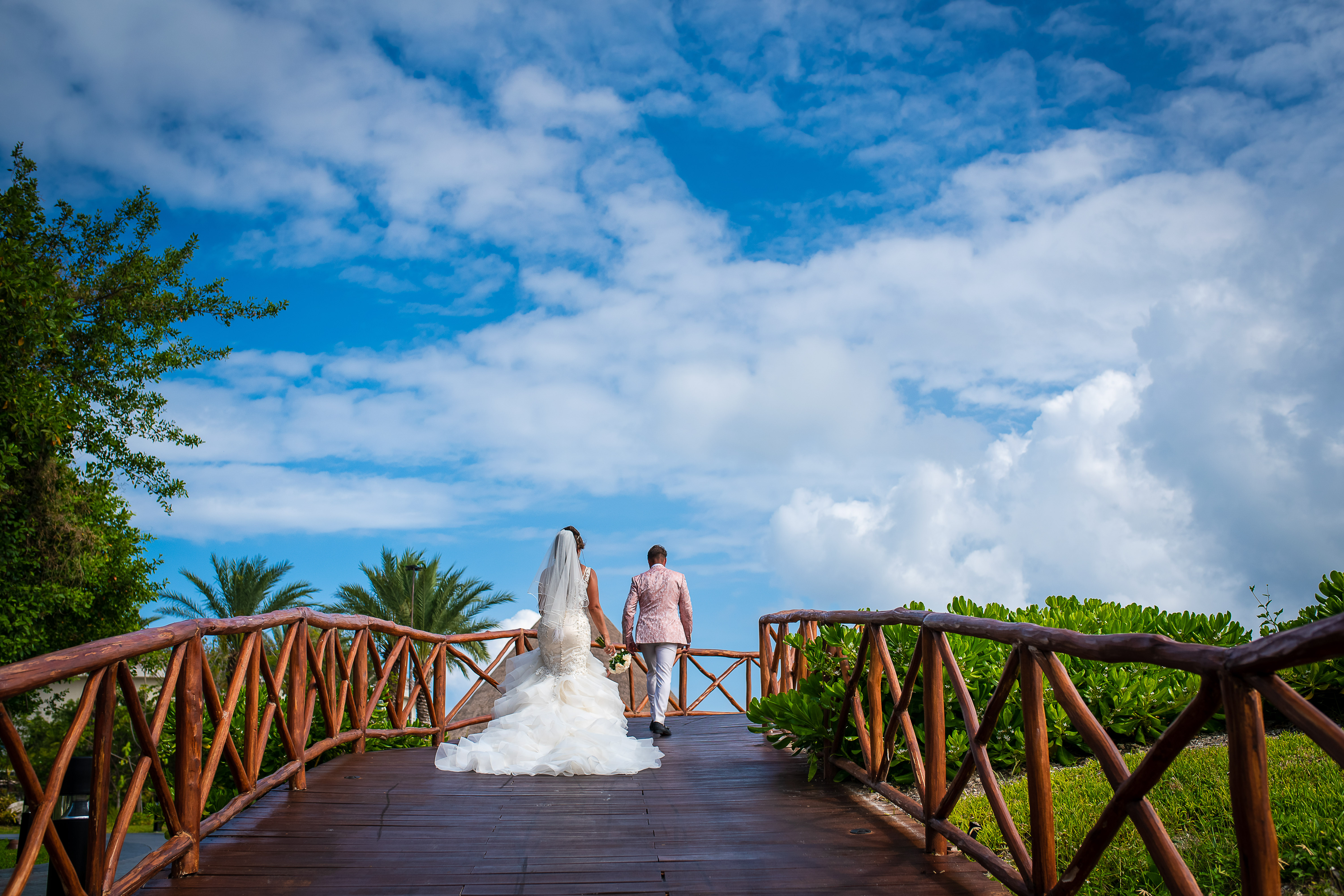bride and groom walking at the bridge with green plants and blue sky in the grand at the moon palace resort