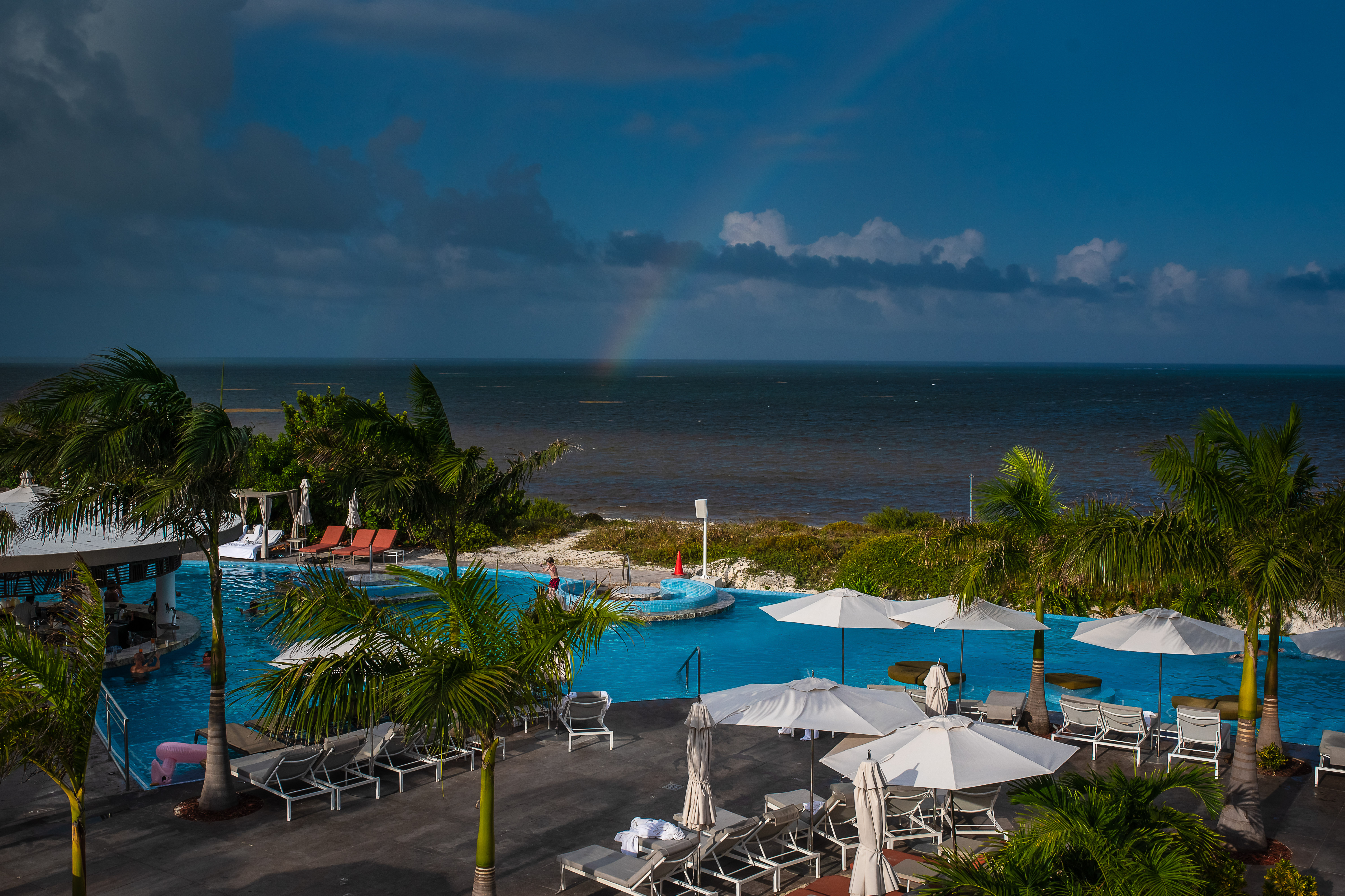 the rainbow in the sea with palm trees pool and blue sky in the grand of the moon palace hotel