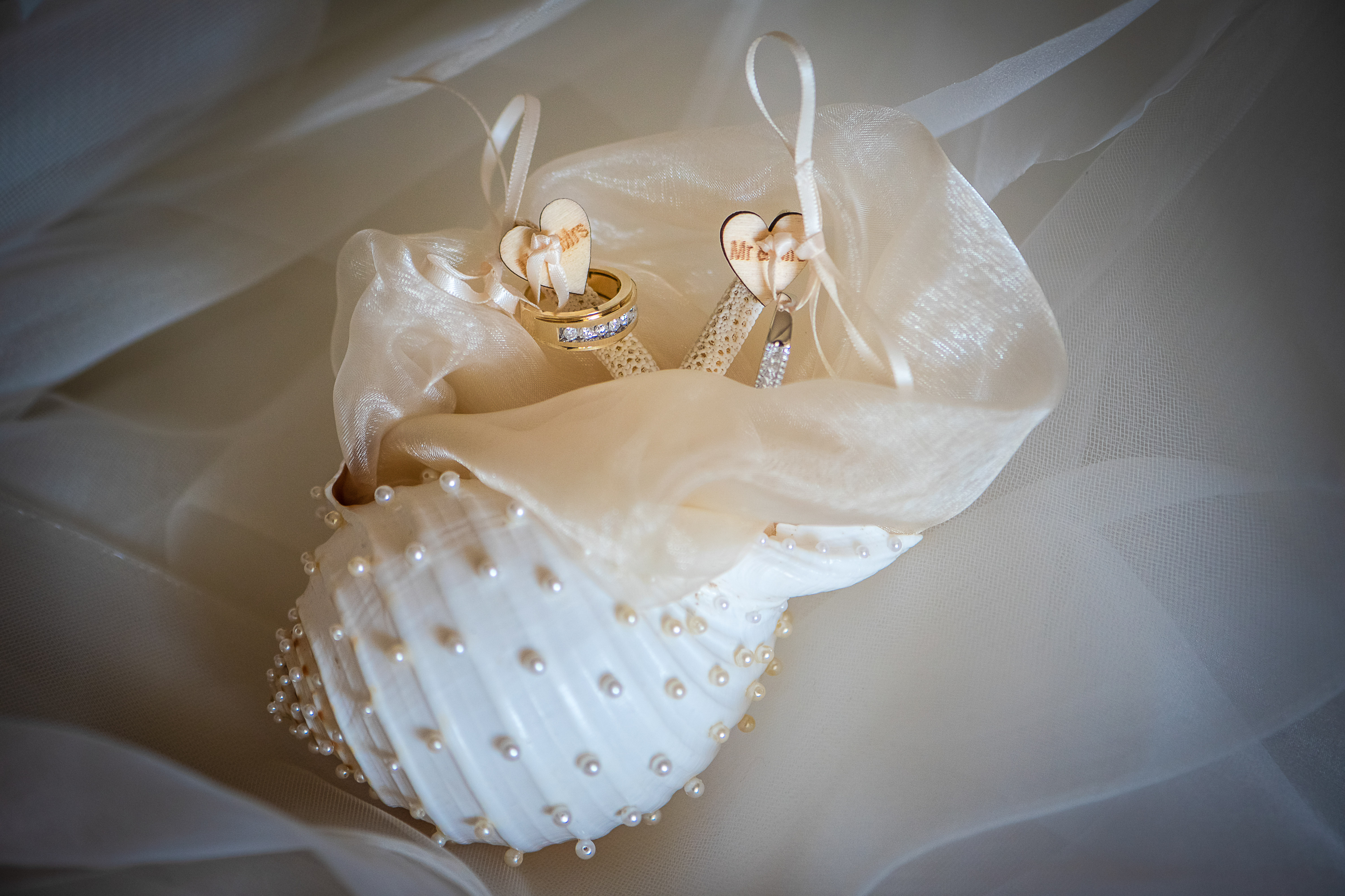 the rings for the bride and groom into of a shell with harts in the grand at moon palace resort