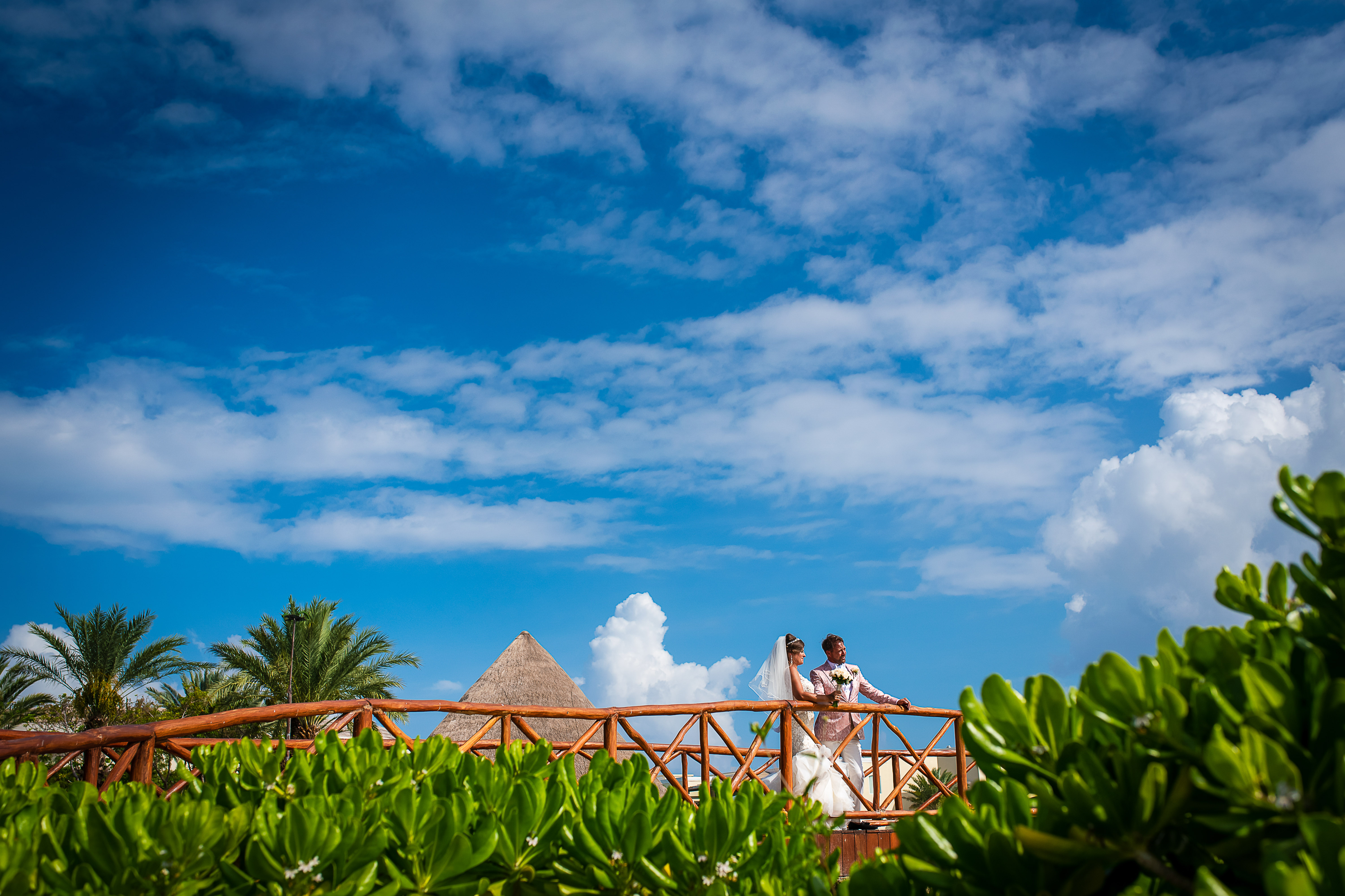 bride and groom posing at the bridge with green plants and blue sky in the grand at the moon palace resort