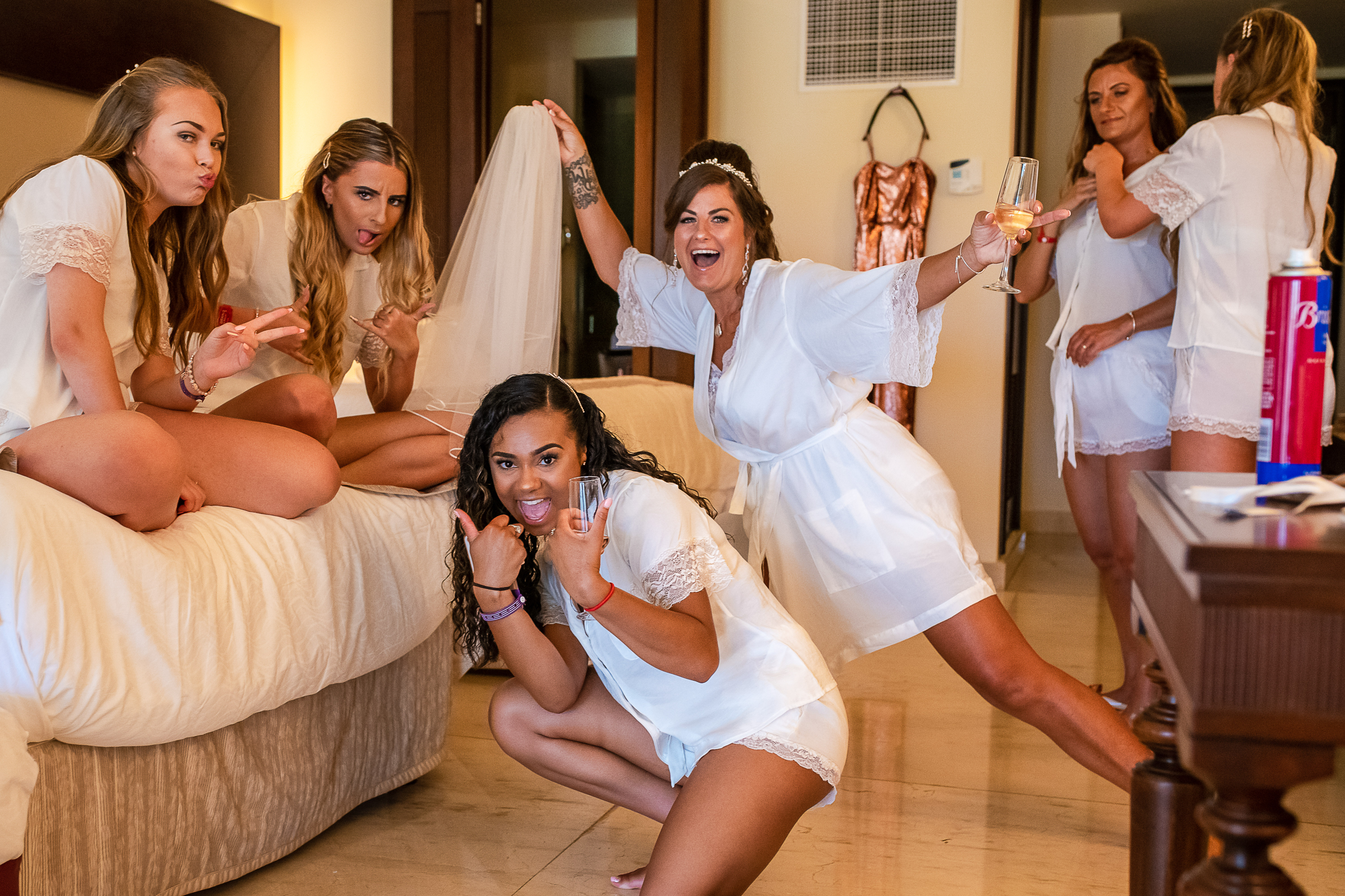 the bride and her bridesmaids having fun time before the ceremony with her underwear